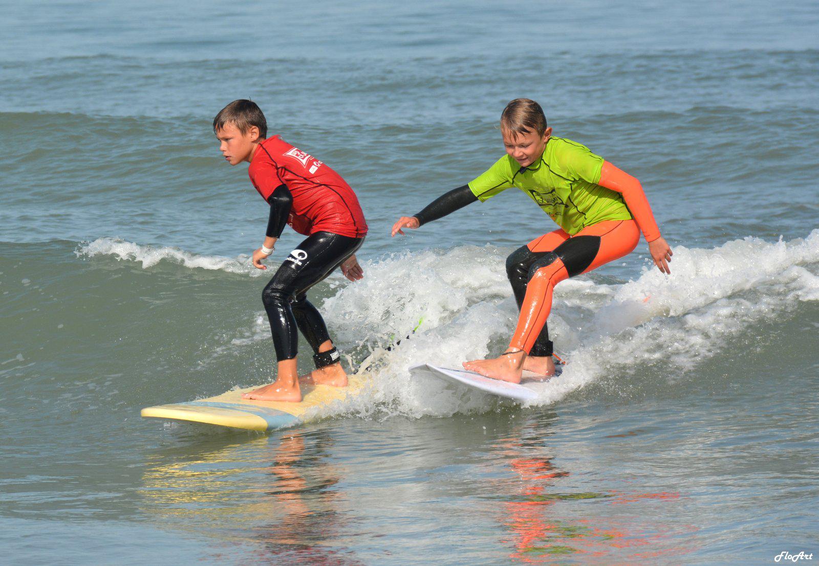 Deux enfants surfent une vague